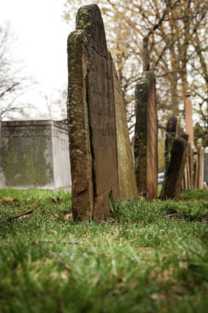 A row of old tombstones in a cemetery. They are really weathered, tilting, and falling apart.