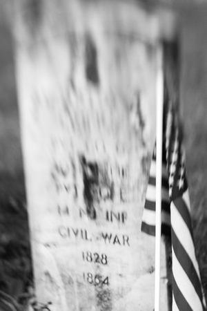 アメリカの国旗は、ニュージャージー州ラーウェイ墓地に古い大学戦争墓石の横に立っています。特殊なレンズは、ボケの効果を生成する使用され