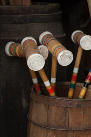 Colorful croquet mallets sit inside a barrel Reklamní fotografie