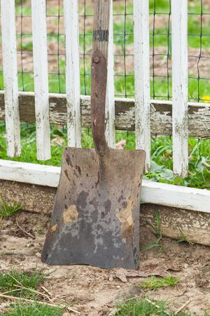 A dirty shovel leans up against a white picket fence on a farm. Reklamní fotografie