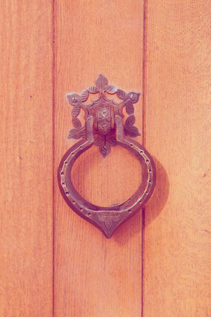 An old metal door knocker on a wooden door