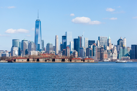 JERSEY CITY, NEW JERSEY - March 6, 2016: The World Trade Center and Lower Manhattan is seen with Ellis Island in the front, from Liberty State Park. Редакционное