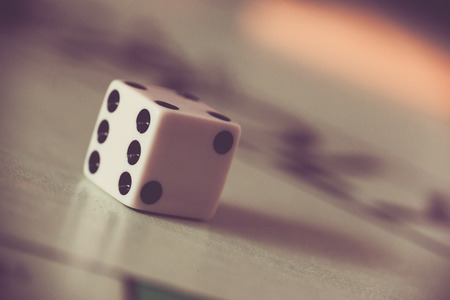 A single dice is isolated on a blurred board game background. Stock Photo