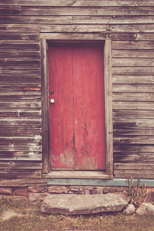 An old door with peeling paint on a wooden sided house.