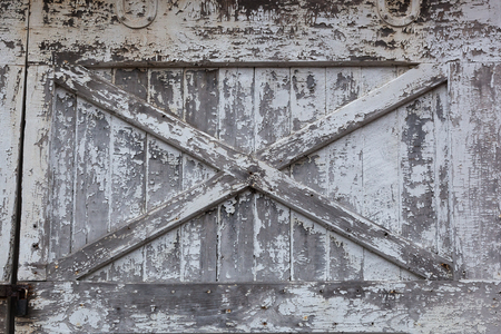 An old white barn door has peeling paint and is in need of repair. Stock Photo