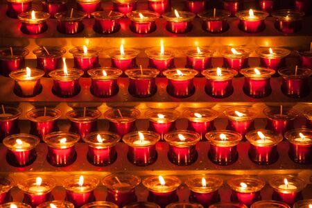Prayer candles, lit inside a church, give off a warm glow. Stock fotó