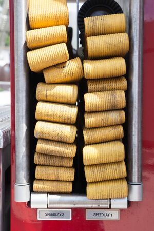 A closeup of the hoses stored in the side of a fire engine truck