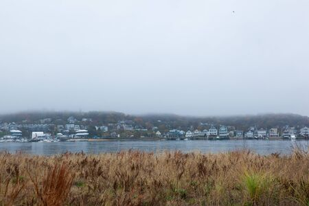 A view of the Atlantic Highlands over the Shrewsbury River on a foggy autumn day. Photo taken from Sandy Hook. The Twin Lights lighthouses are barely visable through the fog.