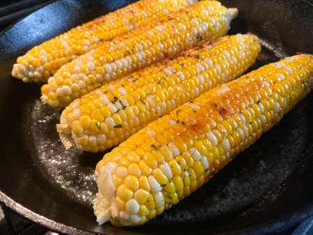 Fresh Jersey Sweet Corn on the cob is cooked in a black cast iron skillet on the stove. It is coated with butter, pepper, and parsley.