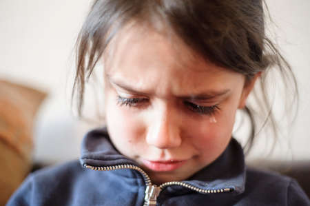 5-year-old girl pings and a tear stops on her sulky face Standard-Bild