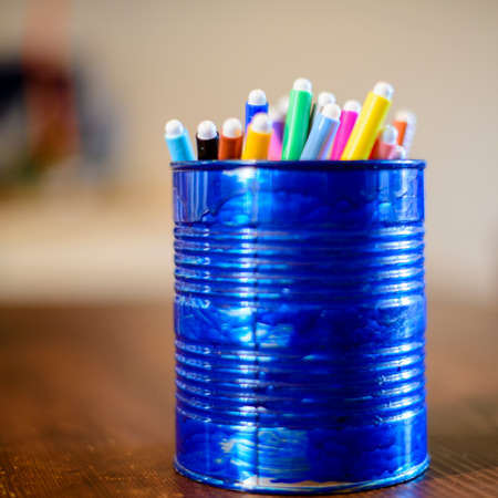 blue pen holder recycled from a tin box for preserves with colored markers Banco de Imagens