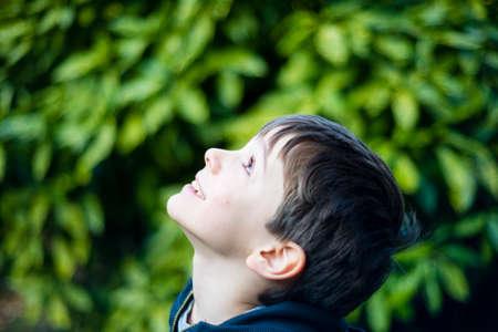 portrait of 7 year old boy outdoor in the garden in winter