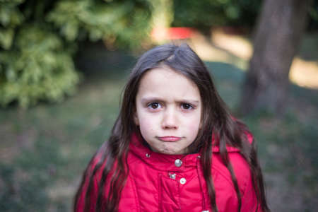portrait of 7 year old girl in outdoor in the garden in winter with red jacket