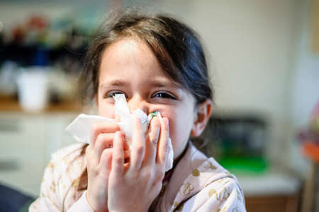 5 year old girl blows her nose with paper towel at home closeup portrait