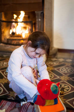 portrait of a 7 year old girl dressed in pajamas playing on the carpet in front of the fireplace