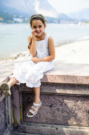 portrait of a smiling 7 year old girl with elegant white colored dress sitting on a wall