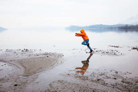 12-year-old boy runs along the beach in winter, dressed in orange jacket Stock Photo