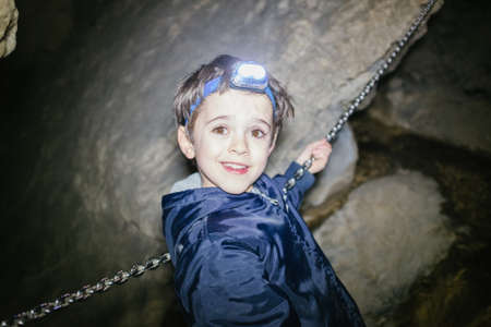 child explores an underground cavern with head-on light