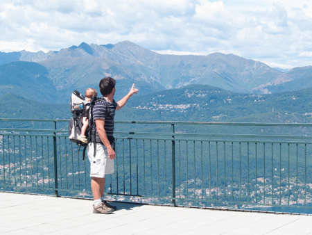 father with a backpack carrying children during an excursion on the mountains of Lake Maggiore indicates the landscape