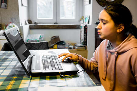 female teenager uses laptop at home in the kitchen on the table