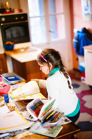 children sitting at the table at home perform school homework