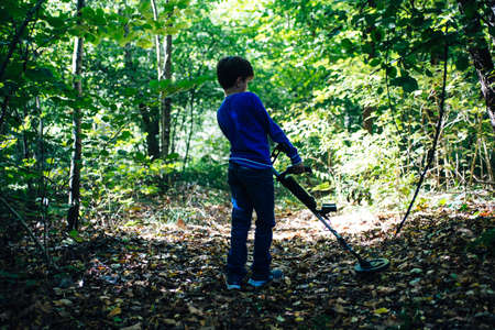 child with metal detector in the woods in spring