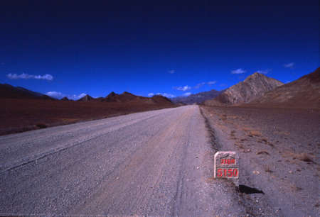 China-Tibet-December 2002 road in the mountains, altitude, gravel with blue sky