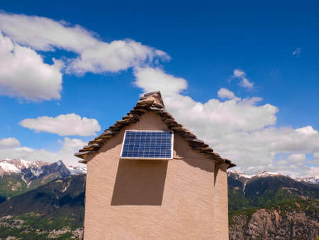 small house on a mountain ridge with solar panel blue sky with few white clouds
