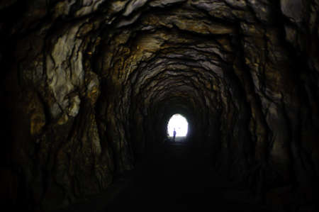 rock tunnel in the mountain human figure at the bottom in the light Imagens