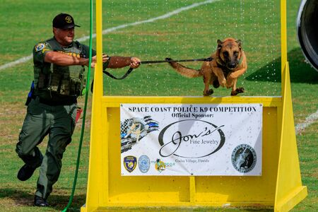Cocoa, Florida / USA - October 12, 2019: A Florida Sheriff's K9 team leaps over a barrier and through a water obstacle during the Space Coast Police K9 Competition Archivio Fotografico - 132890764
