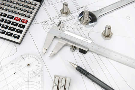 calculator, caliper and bolts on a technical drawing photo