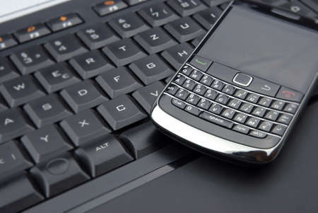 Business cell phone on a keyboard Stock Photo