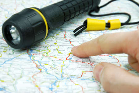 flashlight on a map with pointing finger Stock Photo