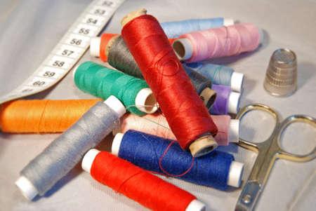 bobbins of different colors, tape measure , finger hat and scissor