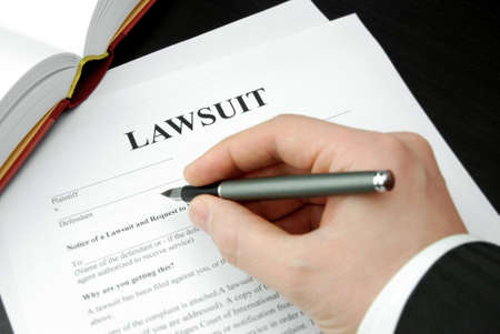 filing documents: lawsuit form with attorneys hand and pen Stock Photo