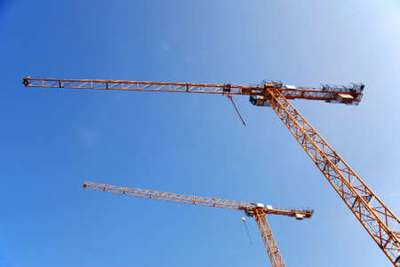 two yellow cranes at a construction site