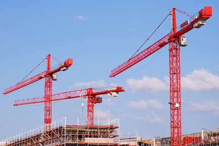 three red cranes on construction site Stock Photo