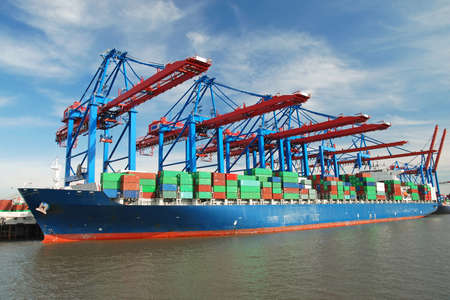 Container ship in harbor port unloading with cranes Stock Photo
