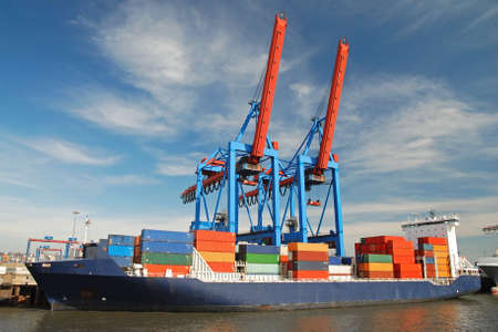 logistics world: blue container ship unloading freight with two cranes