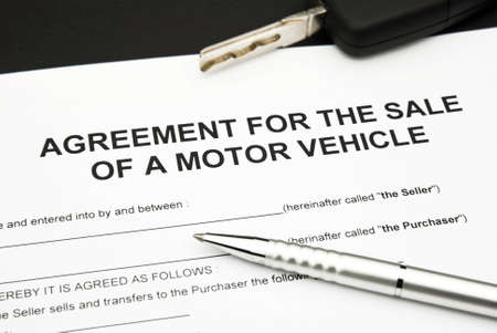 agreement document for sale of a motor vehicle with car key and pen Standard-Bild