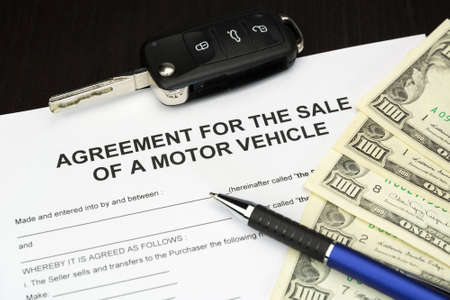motor vehicle: agreement form document for a Sale of motor vehicle with car key, money and pen