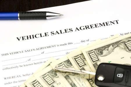 Vehicle sales agreement document contract with car key and pen
