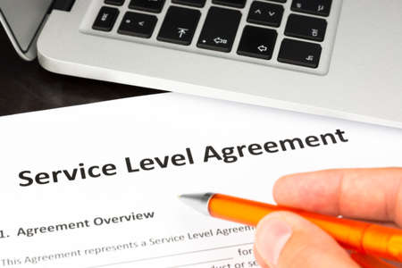 Service Level Agreement Contract Form with Hand and Pen Stock Photo