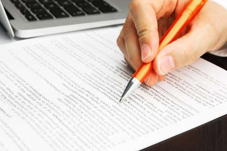 オレンジ色のペン、ノート パソコン、男性の手との契約を歌う