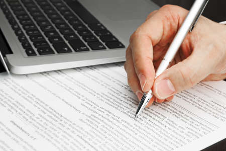 Singining Contract with Laptop and pen and hand