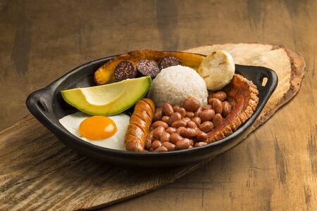 Tray paisa, typical dish at the Antioque? ? a region of Colombia. It consists of chicharrón (fried pork belly), black pudding, sausage, arepa, beans, fried plantain, avocado egg, and rice Foto de archivo