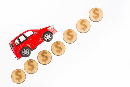 Car model and coins. Concept of auto loan, auto insurance, leasing. Raise and lower the value of the car