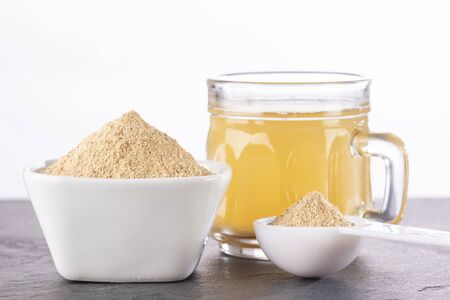 Maca root health drink in a glass with powdered - Lepidium meyenii.