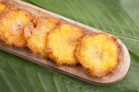 Patacon or toston, fried and flattened pieces of green plantains, a traditional snack or accompaniment in the Caribbean. Imagens