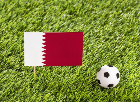 National flag of Qatar with soccer ball in the stadium